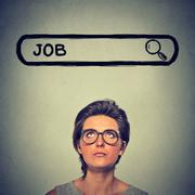 Headshot young woman in glasses thinking looking for a new job isolated on gr - stock photo