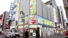 WIDE SHOT OF PEOPLE WALKING BY INTERNET/CYBER CAFE IN TOKYO JAPAN Stock Footage