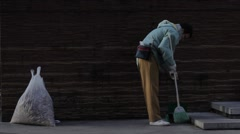 A TEMP WORKER SWEEPING THE STREET AS PEOPLE PASS BY IN JAPAN Stock Footage