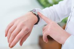 Busy woman looking at her wrist watch - stock photo