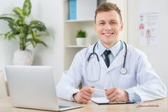 Smiling pediatrician sitting at the table - stock photo