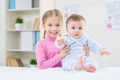 Stock Photo of Little positive girl holding infant
