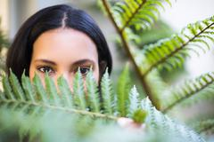 Portrait of a pretty woman looking through leaves outside - stock photo