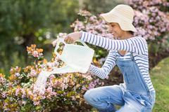 Pretty brunette doing some gardening activities outside - stock photo