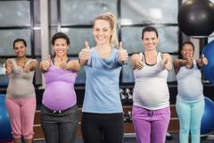 Female trainer and pregnant woman with thumbs up at the leisure center Kuvituskuvat