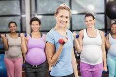 Female trainer with pregnant woman lifting dumbbells at the leisure center Kuvituskuvat