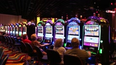 WIDE SHOT OF PEOPLE PLAYING ROWS OF SLOT MACHINES AT CASINO - stock footage