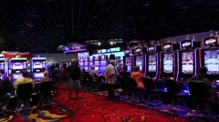 WIDE SHOT OF PEOPLE PLAYING SLOT MACHINES AND PEOPLE WALKING AROUND AT CASINO Stock Footage