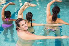 Pregnant woman doing aqua aerobics at the leisure center Stock Photos