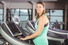 Smiling pregnant woman using treadmill at the leisure center - stock photo