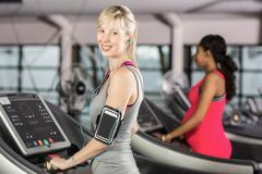 Smiling woman on treadmill with headphones at the leisure center - stock photo