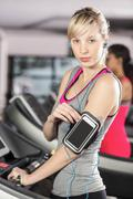 Fit woman on treadmill with headphones at the leisure center - stock photo