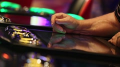 TIGHT SHOT OF A HAND PLAYING BLACK JACK COMPUTER GAME AT CASINO - stock footage