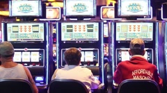 MEDIUM SHOT OF PEOPLE PLAYING SLOT MACHINES AT CASINO - stock footage