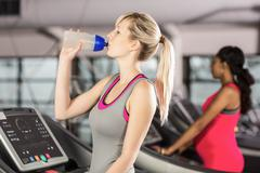 Fit blonde drinking water on treadmill at the leisure center - stock photo