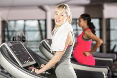 Smiling woman on treadmill looking at the camera at the leisure center - stock photo