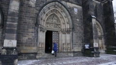 Woman enters the Basilica of St Peter and St Paul in the Prague castle on a wint Stock Footage