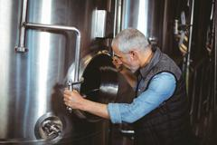 Brewer checking large vats at the local brewery - stock photo