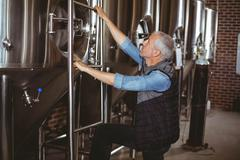 Happy brewer checking large vats at the local brewery - stock photo