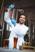 Happy brewer checking beaker of beer at the local brewery - stock photo
