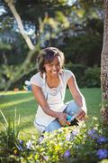 Pretty woman doing some gardening outside - stock photo