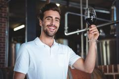 Winemaker examining glass of red wine at winefarm - stock photo