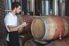 Winemaker taking notes on clipboard on winefarm - stock photo