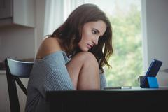 Beautiful brunette watching tablet with chin on knee in the living room at ho - stock photo