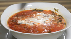 Spoon sour cream is added in white plate with beetroot soup Stock Footage