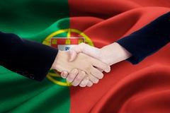 Agreement handshake with flag of Portugal Stock Photos