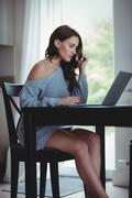 Beautiful brunette using laptop in the living room at home - stock photo