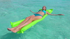 SLOW MOTION: Smiling woman swimming on inflatable airbed in ocean Stock Footage