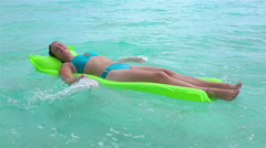 SLOW MOTION: Smiling woman swimming with inflatable air bed mattress - stock footage