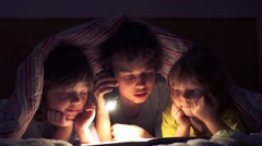 Сhildren read a book under the covers Stock Footage