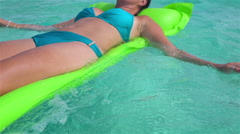 CLOSE UP: Woman laying on water airbed mattress and paddling - stock footage