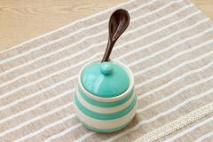 Green pastel porcelain jar and brown spoon with cute fabric. - stock photo