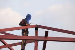 Worker welding the steel to build the roof Stock Photos