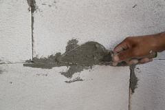 hand using trowel with wet concrete to plastering lightweight Concrete block, - stock photo