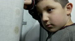 Child leaned on his arm at the window, look depressed for having been punished Stock Footage