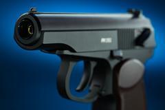 Gun on dark blue background - stock photo