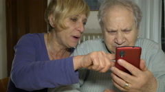 Grey haired old woman with a smartphone in her hand, listen to instruction Stock Footage