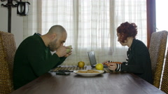 Stock Video Footage of modern couple take breakfast in silence, looking to devices