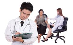 Doctor writting medical report with female doctor measuring blood pressure of Kuvituskuvat