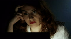Young attractive woman sat at her desk working in a dark room Stock Footage