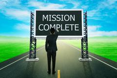 Businessman standing on road and pointing with large sign of mission complete Stock Photos