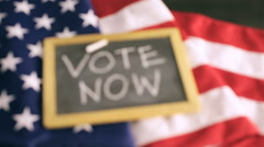 Vote sign on chalk board next to the American Flag. - stock footage