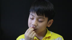 Little Asian child enjoys eating fried chicken with sticky rice - stock footage