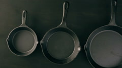 Traditional cast iron skillet on black wood table. Stock Footage