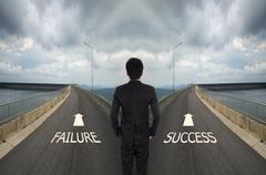 Stock Photo of business man has to decide between two different way, choose Failure or Succe