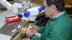 skilled technician modeling a dental prosthesis thanks to a high precision tool - stock footage